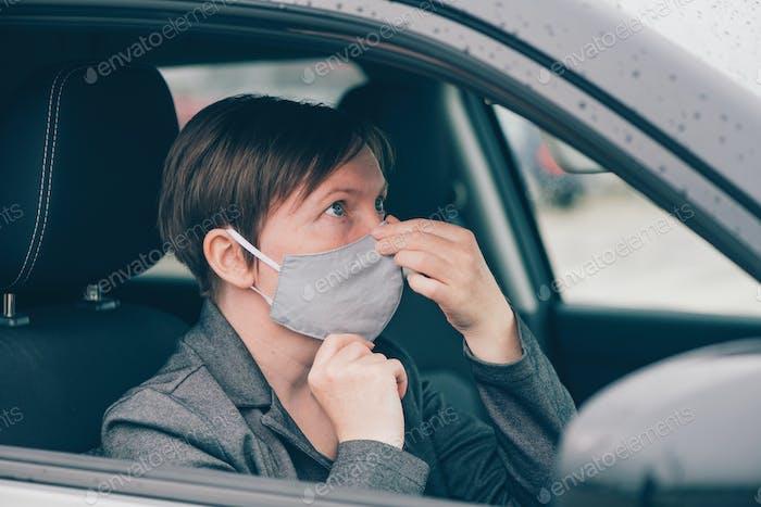 Mujer con mascarilla protectora en el coche durante pandemias de Covid-19