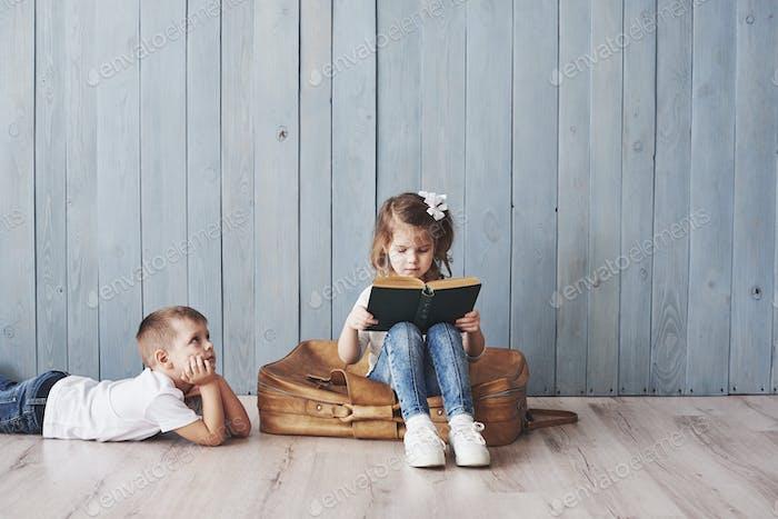 Glückliches kleines Mädchen und Junge lesen interessante Buch trägt eine große Aktentasche und lächelnd