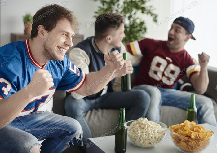 Mates hanging out and watching a game