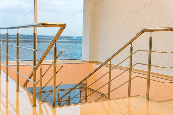 Modern beige airport staircase with the chrome handrails