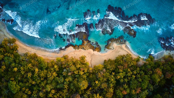 Scenic aerial shot of a tiny rock island surrounded by waves of the crystal clear ocean