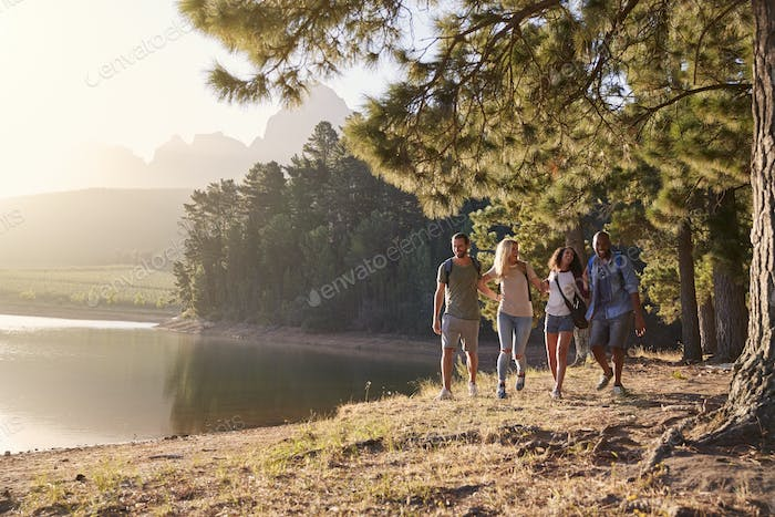 Group Of Young Friends Enjoying Walk By Lake On Hiking Adventure