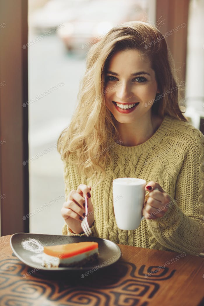 Charming girl drinking cappuccino and eating cheesecake