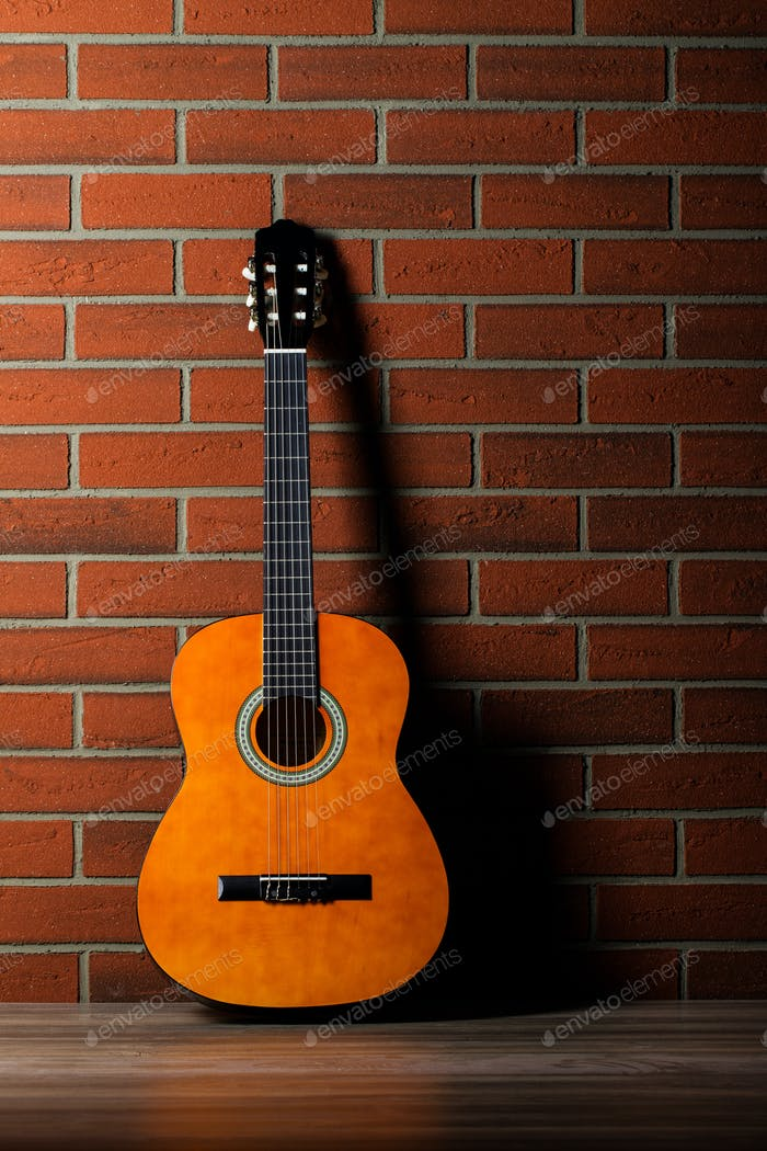 Acoustic guitar leaning against a wall.