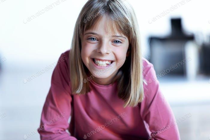 Hübsches blondes Mädchen, das zu Hause in die Kamera schaut.