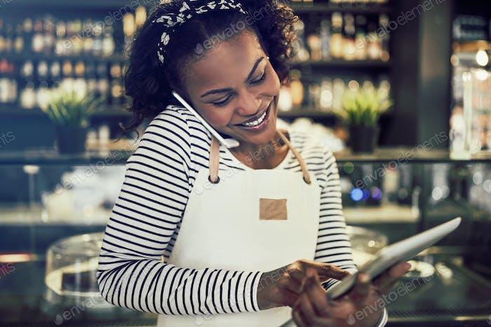 Lächelnd afrikanischen Cafébesitzer Reservierungen über das Telefon