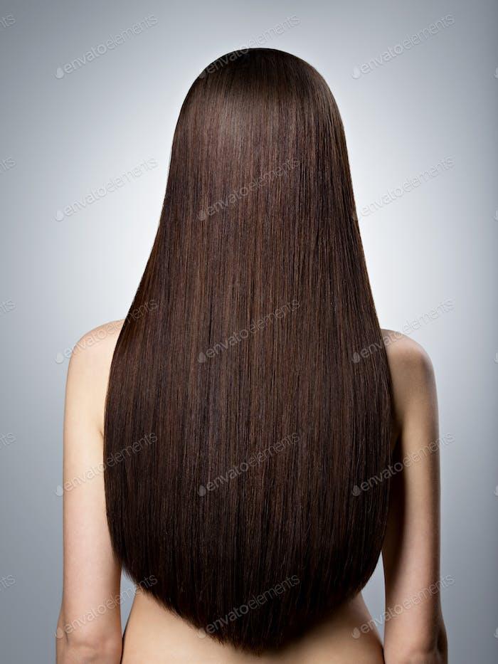 Frau mit langen braunen glatten Haaren. Rückansicht