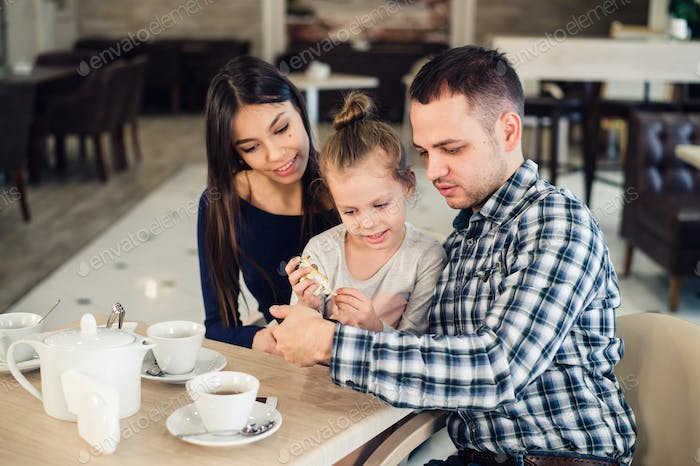 family, parenthood, technology people concept - happy mother, father and little girl having dinner