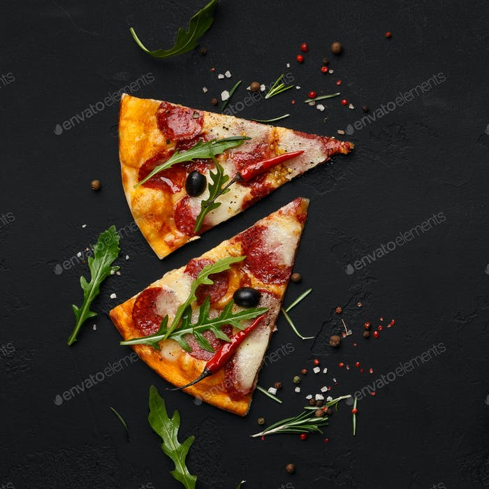 Pizza slices with rocket salad on black background