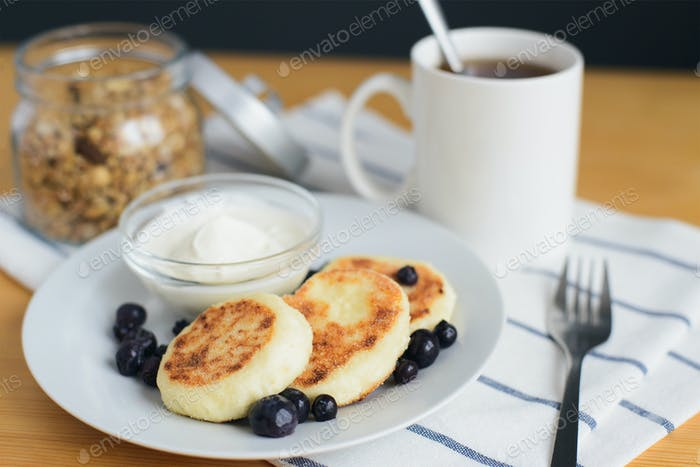 fried circular syrniki, tvorozhniki or cheese cake with sour cream and hot drink