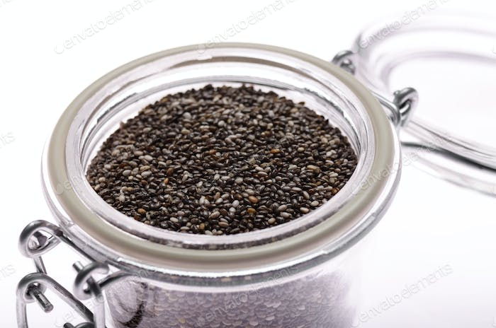 Raw Chia seeds in clear glass airtight jar on white background