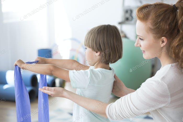 Physiotherapist supporting kid