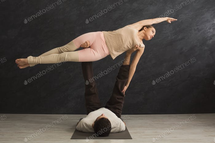 Young couple practicing acroyoga on mat together