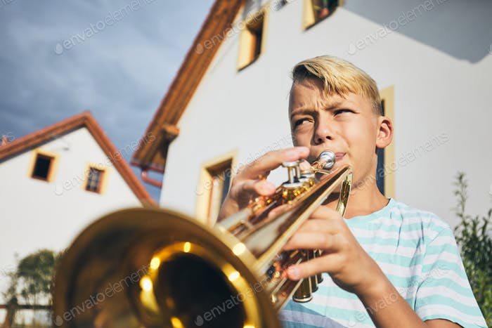 Little boy playing the trumpet