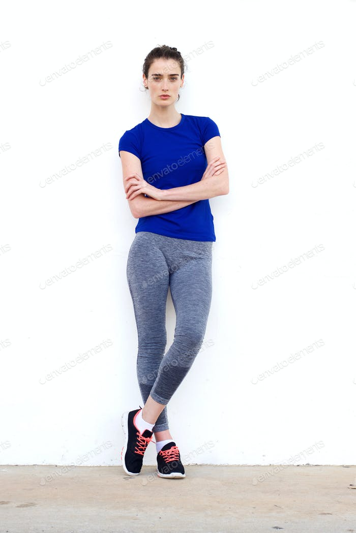 Sporty woman leaning against white wall with arms crossed