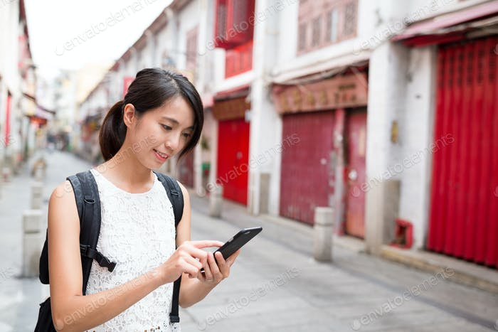 Woman using cellphone to search for wifi