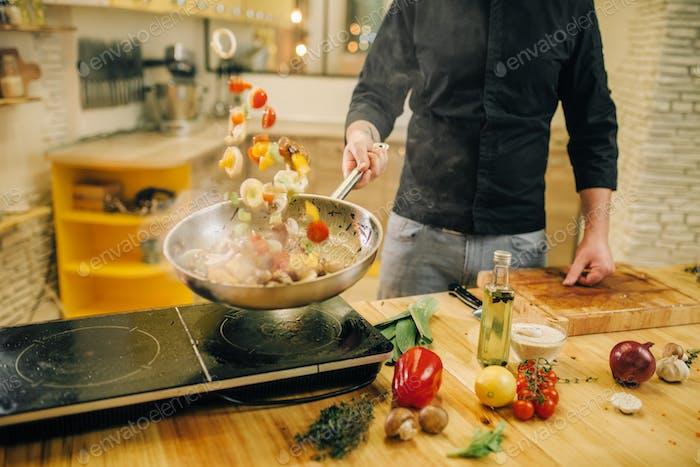 Männlicher Koch Kochen Fleisch mit Vetables in die Pfanne