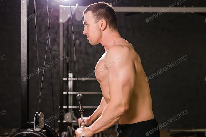 handsome bodybuilder works out excercise in gym