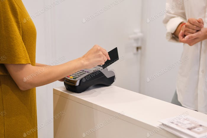 Close up woman paying with credit card in store