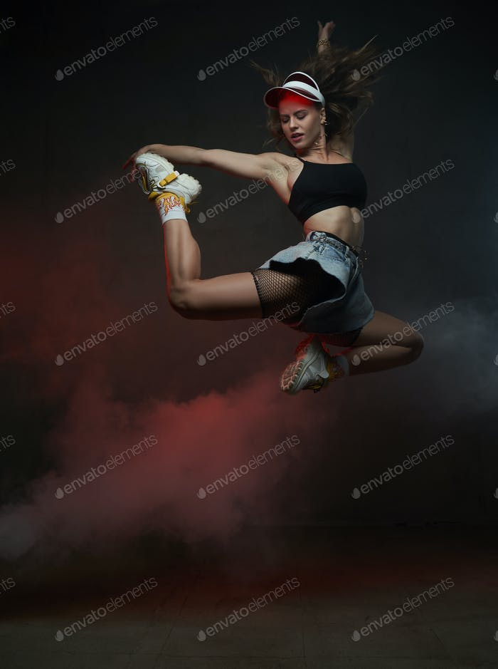 Energetic graceful dancer with cap jumping and posing in studio