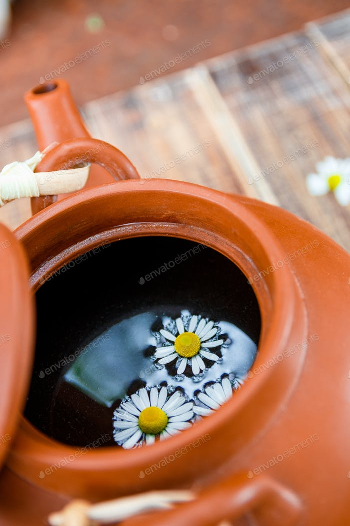Closeup of Open brown teapot with tea and flower of chamomile on wooden background. Tea concept.