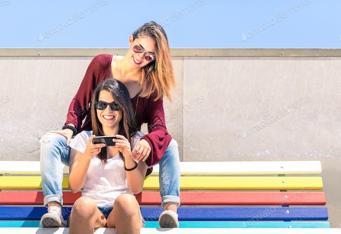 Mejores amigos disfrutando de tiempo juntos al aire libre con el smartphone