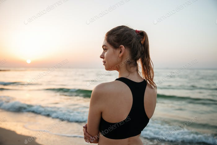 Young woman resting after jogging training on beach at sunset