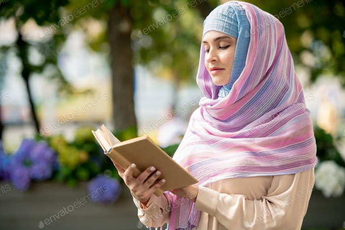 Young muslim female with open book reading stories or novel