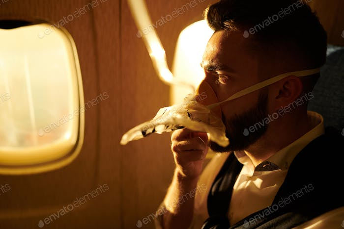 Man Breathing Oxygen in Plane