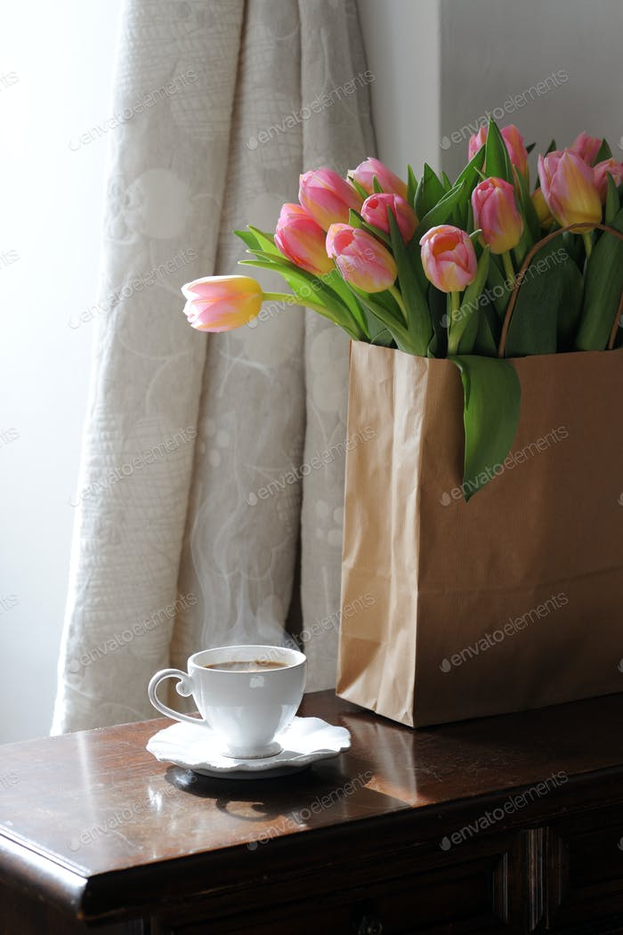 Cup of coffee and beautiful tulips