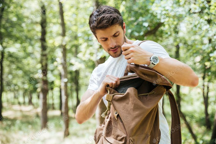 Man looking something in backpack at forest