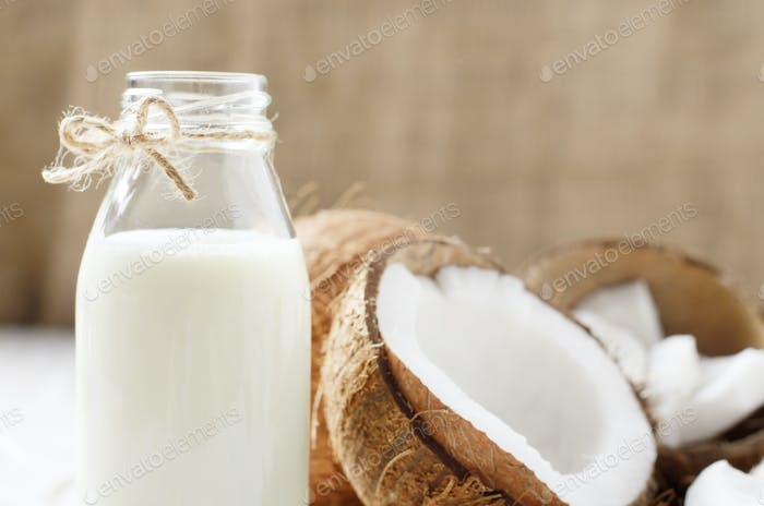 Milk or yogurt in glass bottle on white wooden table with coconu