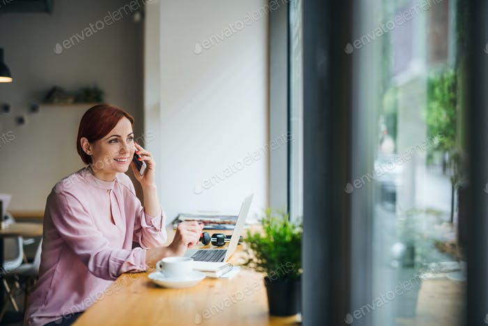 A woman with coffee and telephone sitting at the table in a cafe, making a phone call.