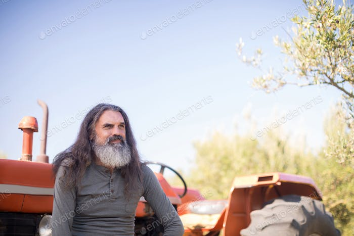 Thoughtful man sitting against tractor in olive farm