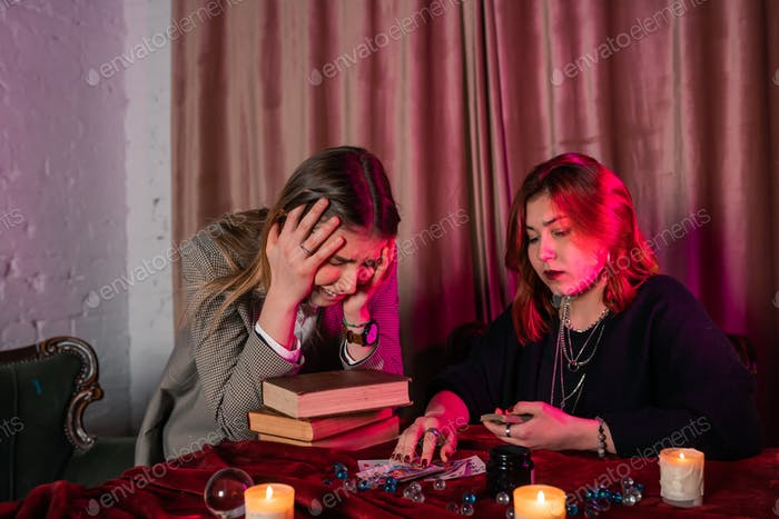 Fortune teller forecasting the future to woman with cards