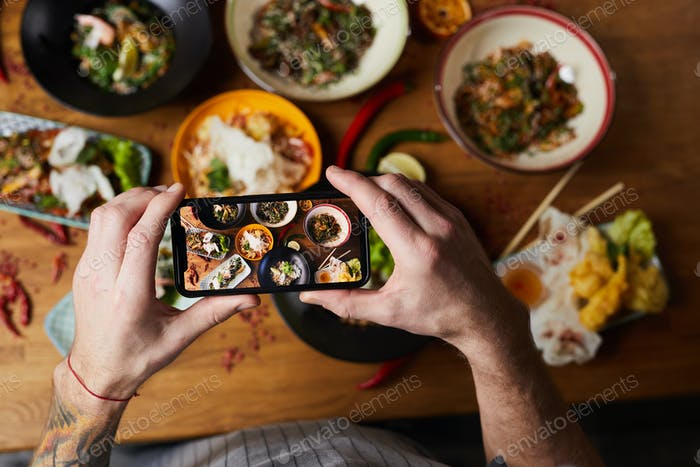 Chef Taking Photo of Asian Food