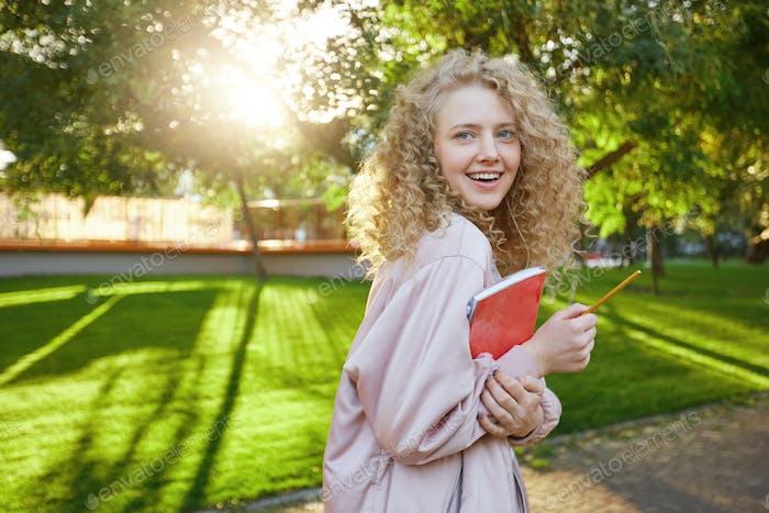 Junge Schüler mit blonden Haaren spazieren mit einem roten Notizbuch und einem Bleistift durch den Park