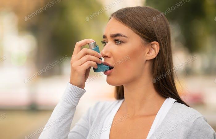 Girl Having Asthmatic Attack Using Inhaler Walking In City