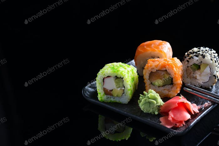 Large sushi sets with lots of sushi, roll . Stylish sushi sets on a black ceramic plane and table