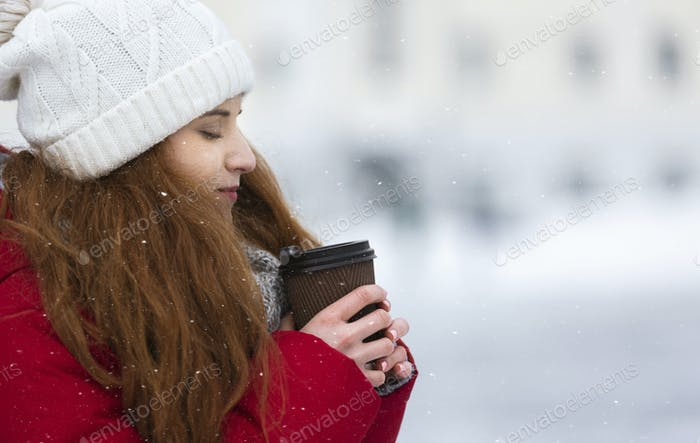 Freezing girl drinking hot coffee during walk on winter day