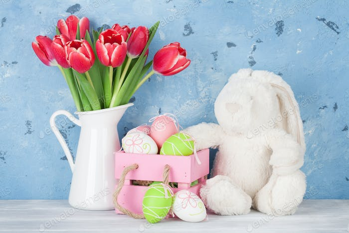 Red tulip flowers, eggs and easter rabbit toy