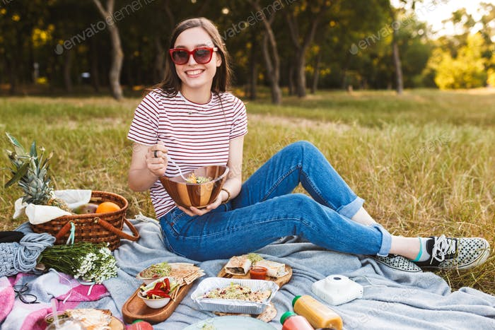 Beautiful girl in sunglasses holding bowl with salad sitting on