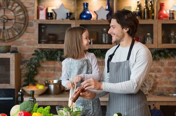 Joyful Young Dad And Little Daughter Cooking Vegetable Salad For Lunch Together