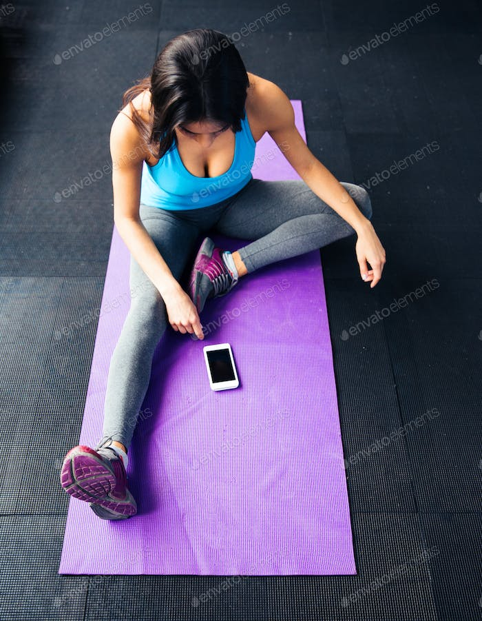 Woman sitting on the yoga mat and looking on smartphone