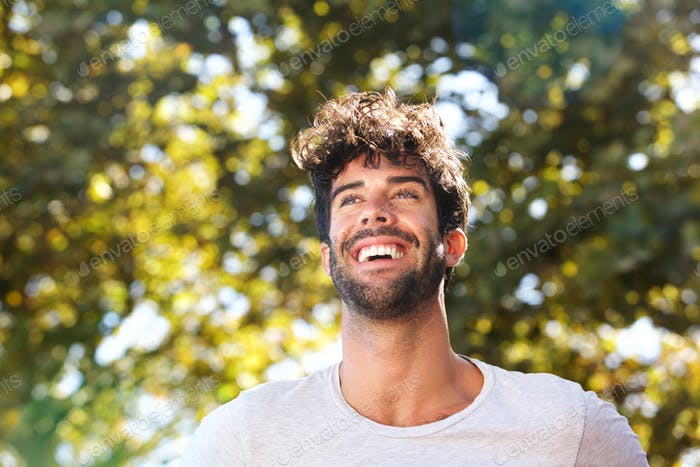 Close up laughing handsome man with beard outside in nature