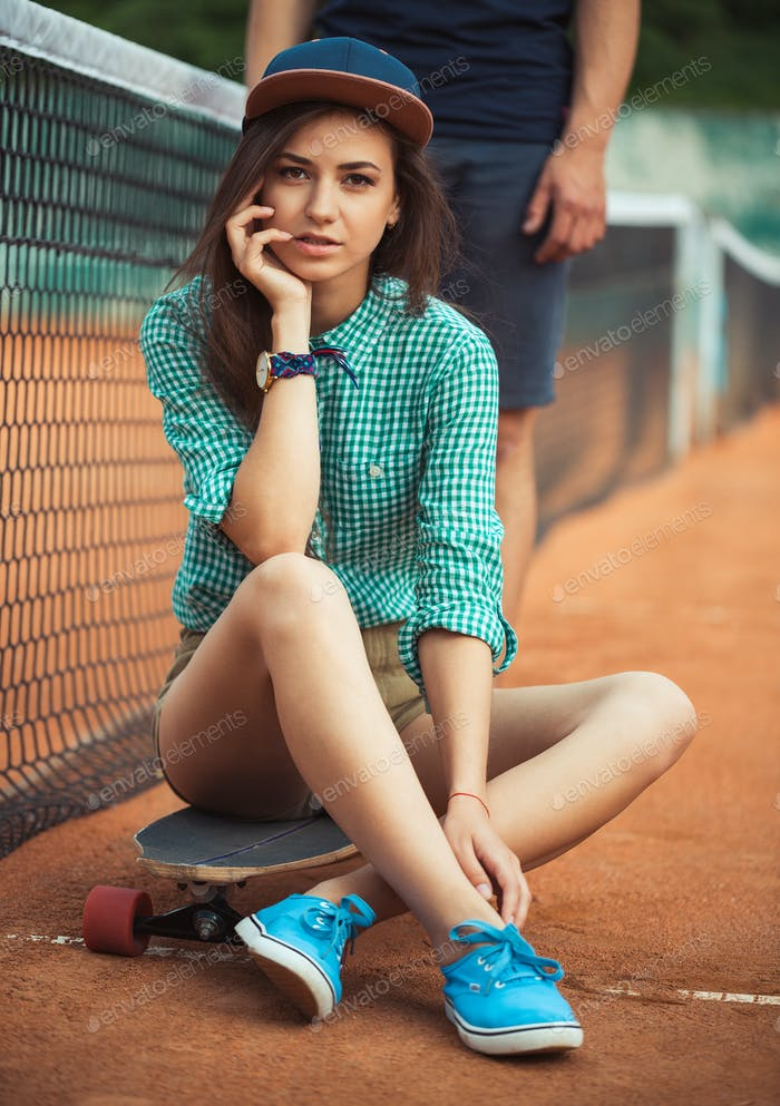 Girl sitting on a skateboard on the tennis court