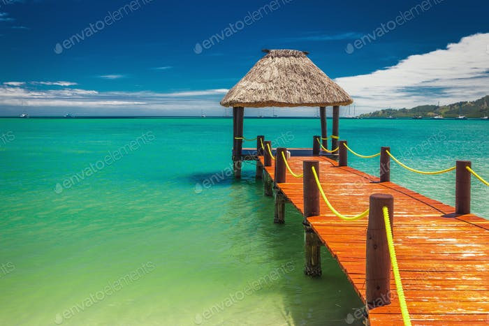 Red wooden jetty extending to tropical ocean in Fiji