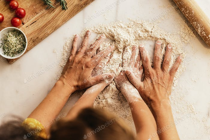 Little girl kneading flour with her mother.