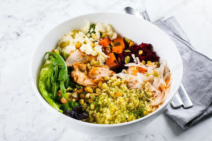 Healthy lunch bowl. Salad with meat, cheese, bulgur and vegetables on marble background
