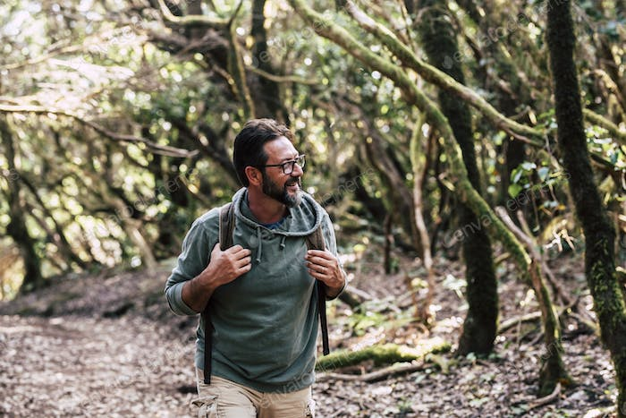 Portrait of man with backpack enjoying outdoor leisure activity walking in the wood forest alone